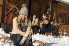 Jeune femme avec le cottage d'hiver de neige d'amis Images stock