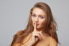 Jeune femme avec le doigt sur des lèvres, sur le fond gris Photographie stock libre de droits