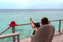 Jeune femme avec le fonctionnement rouge de chapeau sur un comprimé dans une destination tropicale images libres de droits