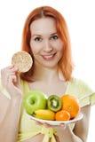 Jeune femme avec le fruit d'une plaque et des pains Image stock