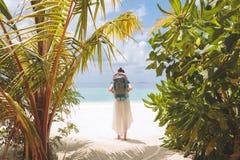 Jeune femme avec le grand sac ? dos marchant ? la plage dans une destination tropicale de vacances image stock