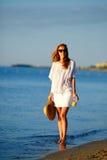 Jeune femme avec le jus d'orange à disposition dans des vêtements blancs sur la plage Photographie stock