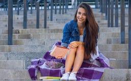 Jeune femme avec le livre dans sa main se reposant sur des escaliers à urbain photographie stock libre de droits