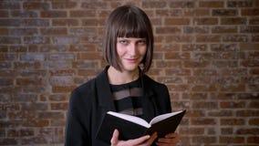 Jeune femme avec le livre de lecture court de coupe de cheveux et sourire à l'appareil-photo, d'isolement sur le fond de brique clips vidéos