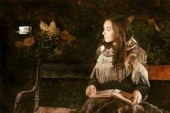 Jeune femme avec le livre et la tasse de thé faisante de la lévitation sur un banc de parc Images libres de droits