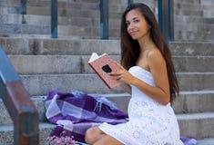 Jeune femme avec le long livre de lecture de cheveux se reposant sur des escaliers à urbain image libre de droits