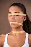Jeune femme avec le mètre qui ferme sa bouche Photo libre de droits