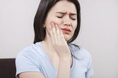 Jeune femme avec le mal de dents photo stock