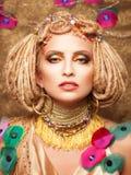 Jeune femme avec le maquillage de mode sur le brun Image stock