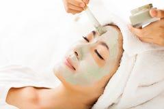 Jeune femme avec le masque de massage facial d'argile Photos stock