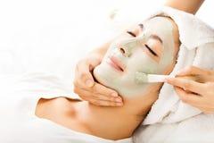 Jeune femme avec le masque de massage facial d'argile Photo stock