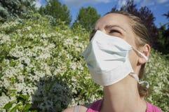 Jeune femme avec le masque protecteur au parc de floraison Image stock
