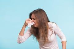 Jeune femme avec le mouchoir La fille malade d'isolement a l'écoulement nasal sur le fond bleu Photos libres de droits
