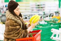 Jeune femme avec le panier à provisions choisissant la banane pendant les achats au supermarché photographie stock