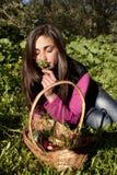 Jeune femme avec le panier des oeufs sélectionnant des fleurs Image libre de droits