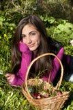 Jeune femme avec le panier des oeufs sélectionnant des fleurs Photos stock