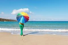 Jeune femme avec le parapluie coloré sur la plage photos stock