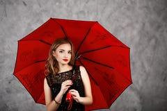 Jeune femme avec le parapluie rouge Image stock