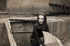 Jeune femme avec le parapluie se reposant près de la vieille maison Photo stock