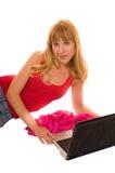 Jeune femme avec le PC sur l'étage Images stock