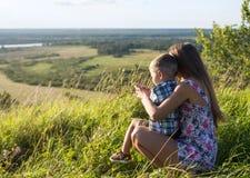 Jeune femme avec le petit garçon s'asseyant dans la haute herbe sur la colline Images libres de droits