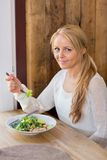 Jeune femme avec le plat de la salade dans le restaurant Photographie stock libre de droits
