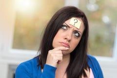 Jeune femme avec le point d'interrogation sur son front photographie stock libre de droits