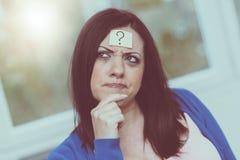 Jeune femme avec le point d'interrogation sur son front images stock