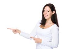 Jeune femme avec le point de doigt à de côté Images libres de droits