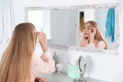 Jeune femme avec le problème de perte de cil regardant dans le miroir photos libres de droits