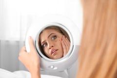 Jeune femme avec le probl?me de perte de cil regardant dans le miroir photo libre de droits