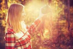 Jeune femme avec le rétro appareil-photo de photo prenant le selfie Photographie stock libre de droits