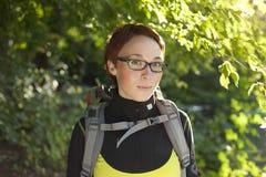 Jeune femme avec le sac à dos dans bois Hausse à l'été Image stock