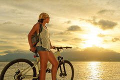 Jeune femme avec le sac à dos se tenant sur le rivage près de son vélo Photos libres de droits