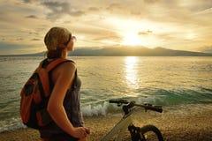 Jeune femme avec le sac à dos tenant sur le rivage près du sien le vélo Image stock