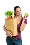 Jeune femme avec le sac d'épicerie et la pomme verte Photo stock