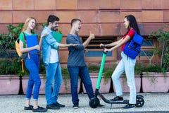 Jeune femme avec le scooter électrique rencontrant des amis images stock