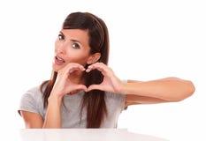 Jeune femme avec le signe d'amour vous regardant Images libres de droits