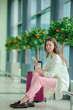 Jeune femme avec le smartphone dans l'aéroport international Passager de ligne aérienne dans un avion de attente de vol de salon  Images stock