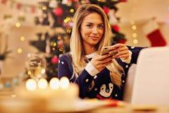 Jeune femme avec le smartphone pendant le Noël à la maison Photographie stock libre de droits