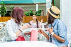 Jeune femme avec le smartphone regardant les amis de sourire avec le panier Image stock