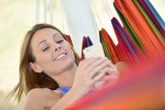Jeune femme avec le smartphone utilisant le comprimé photo stock