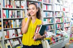 Jeune femme avec le téléphone dans la librairie Photo stock