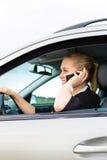 Jeune femme avec le téléphone dans le véhicule Photographie stock libre de droits