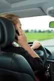 Jeune femme avec le téléphone dans le véhicule Image stock
