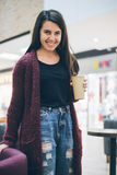Jeune femme avec le téléphone intelligent et la tasse de café tenant le café proche Photos stock