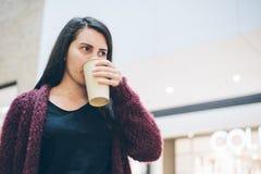 Jeune femme avec le téléphone intelligent et la tasse de café tenant le café proche Photo stock