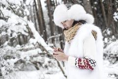Jeune femme avec le téléphone portable dans la forêt d'hiver Photo stock