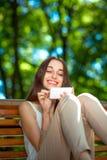 Jeune femme avec le téléphone portable en parc Photographie stock