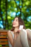 Jeune femme avec le téléphone portable en parc Image stock
